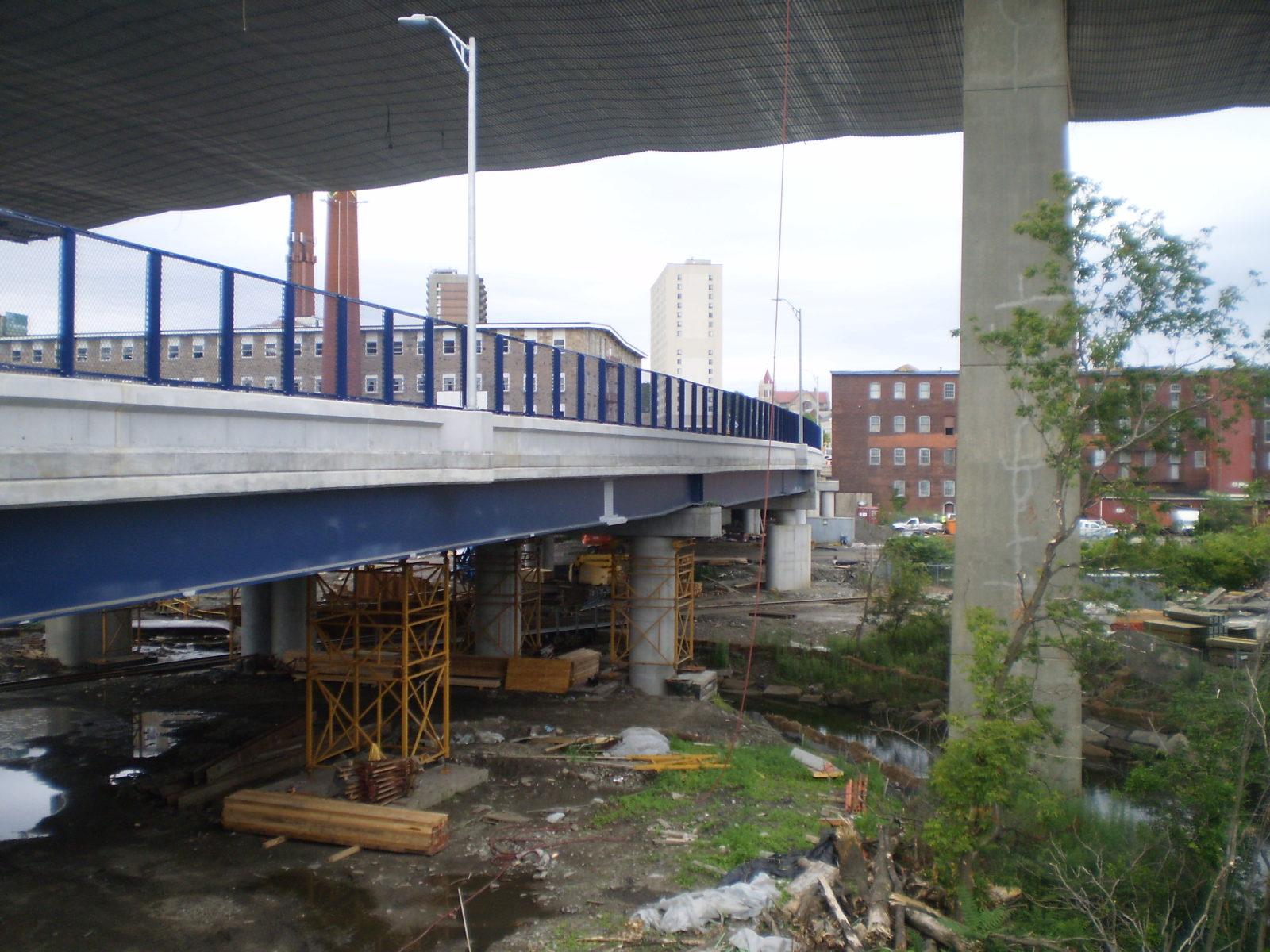 small blue fenced bridge under highway bridge