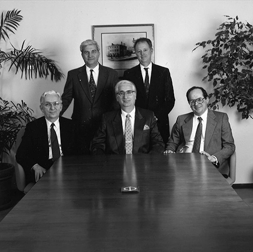 black and white photo of founders sitting at the end of a table