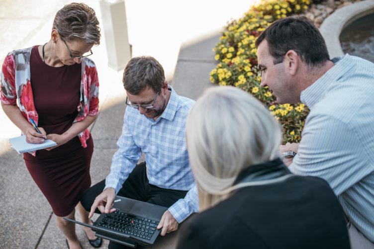 people gathering around man with laptop