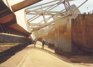 two men walking through dam structure