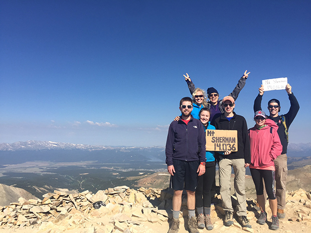 people holding up signs at the top of a mountain