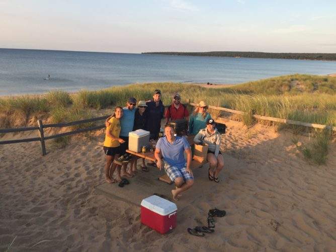 people sitting at a picnic table on sand