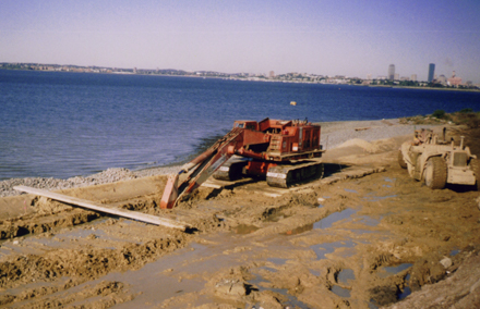 construction crane in mud at water's edge