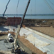 construction cranes on dam site by the water
