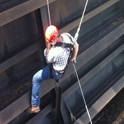 construction worker in hard hat being lowered beside wall
