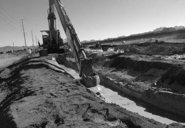 crane digging path for water in dirt