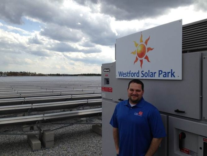 GEI employee standing in front of Westford Solar Park sign
