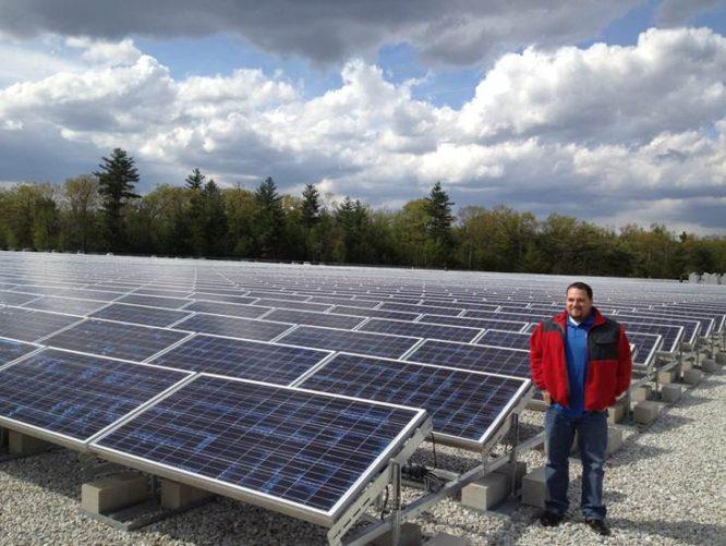 GEI employee by solar panels