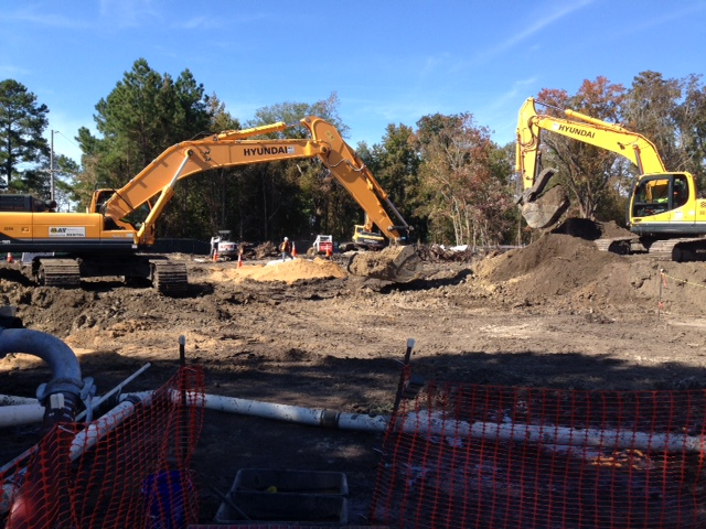 two construction cranes excavating