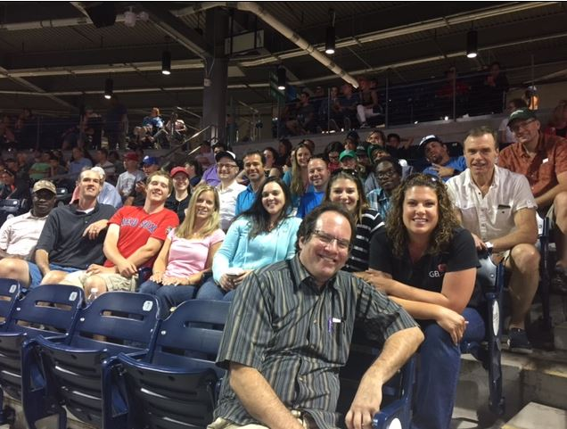 GEI employees sitting at a baseball game