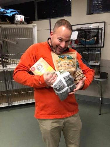 man carrying dog treats and towels