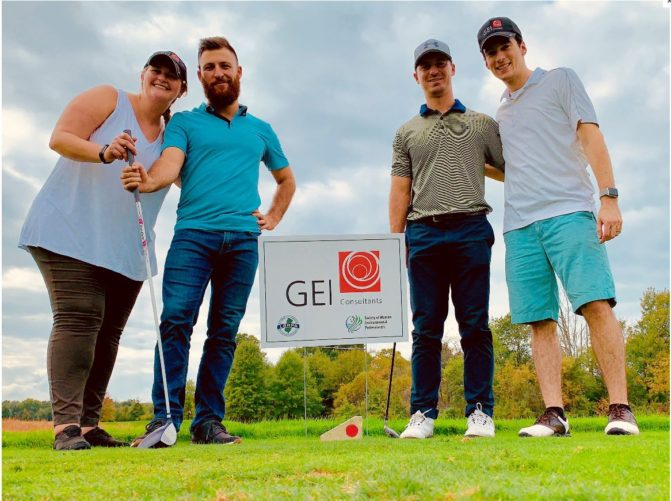 GEI Consultants employees with golf clubs on course