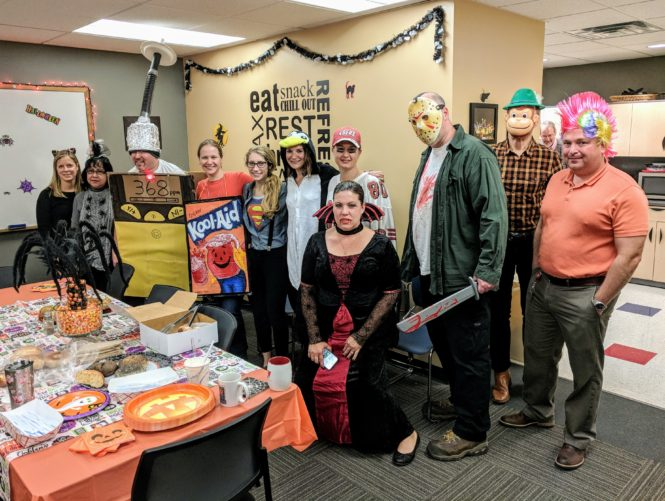 team in various costumes at Halloween party
